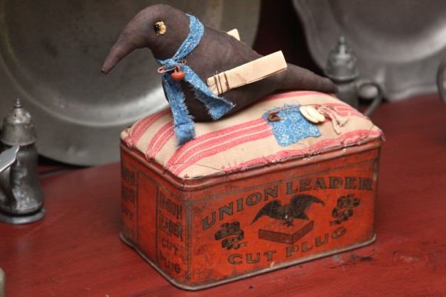 "Paper winged black bird on antique ""Union Leader"" tin"