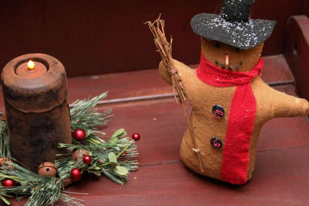 Snowman with red scarf and broom